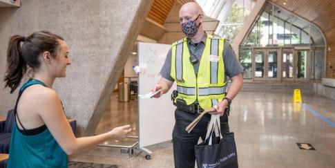 COVID Ambassador hands a face mask to a campus community member
