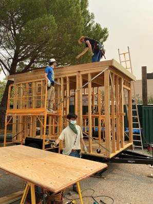 Sean Ticknor and members of his Big Skills Tiny Home team work on structures that help the high school-aged team members learn many aspects of homebuilding. (Courtesy of Big Skills Tiny Homes)