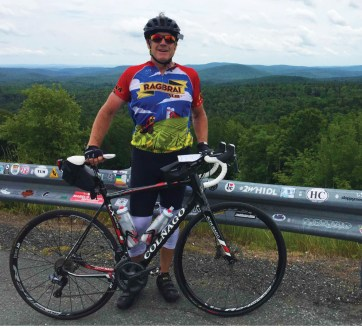 photo of Bruce standing by his bike on a mountain road