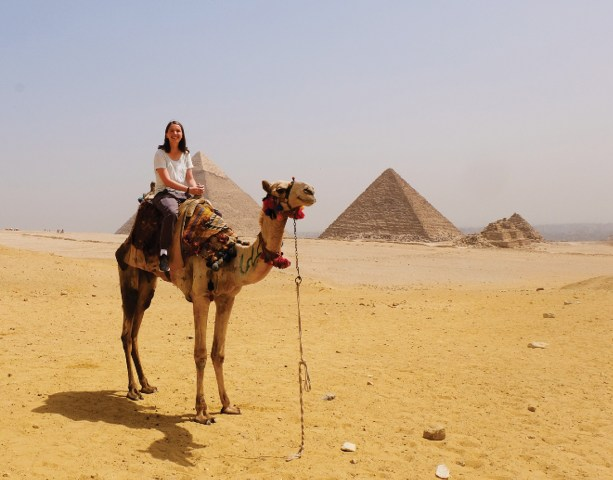 photo of Taylor on a camel with pyramids in the background