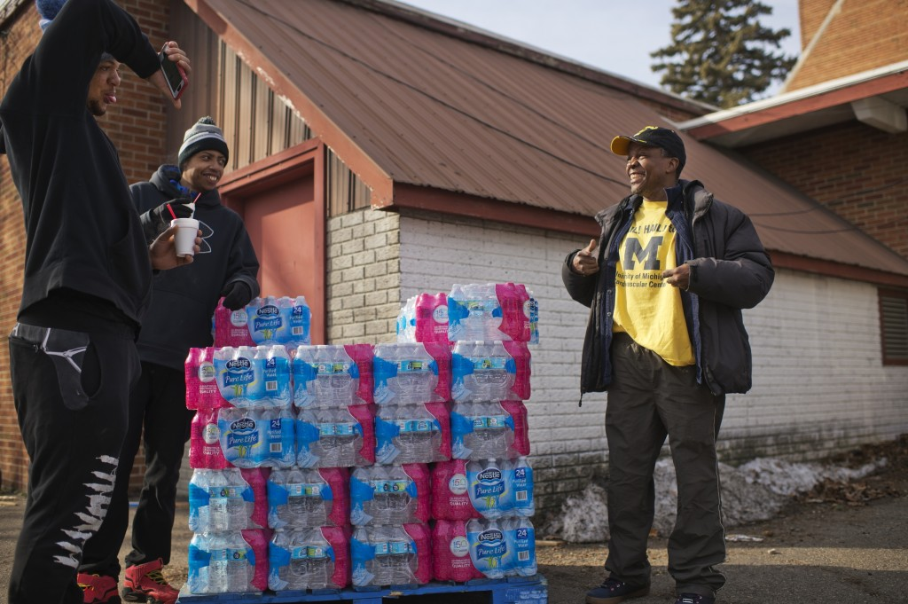 UNITED STATES - FEBRUARY 23: Michigan State fan Immanuel Stinson, far left, taunts Walter Simmons, for wearing a University of Michigan shirt as Tirrell Mills, looks on, at a water distribution area at the St. Mark Baptist Church in Flint, Mich., February 23, 2016. The water supply was not properly treated after being switched from Lake Huron to the Flint River and now contains lead and iron. (Photo By Tom Williams/CQ Roll Call)