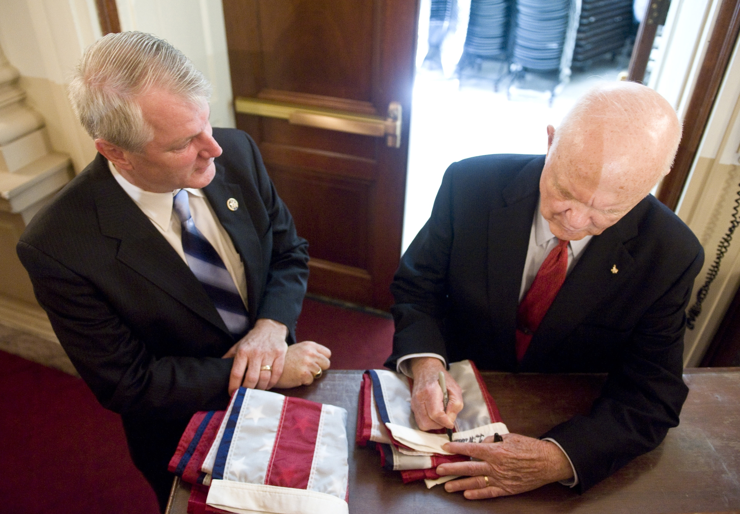 Rep. Brian Baird, D-Wash., left, watches as astronaut and former Sen. John Glenn, D-Ohio, signs two flags for Baird's twin sons during the tribute event to the Apollo 11 astronauts celebrating the 40th anniversary of the first moon landing on Tuesday, July 21, 2009. (CQ Roll Call File Photo)