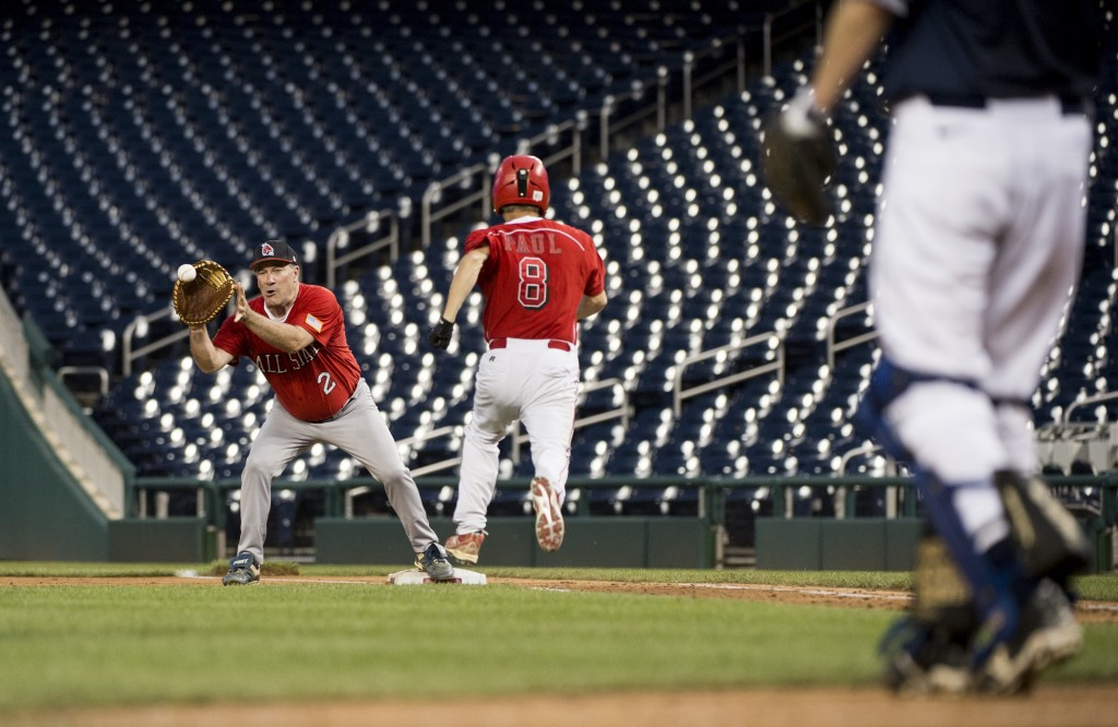 Sen. Joe Donnelly, D-Ind., catches the throw to first base after Sen. Rand Paul, R-Ky., bunted during the Roll Call Congressional Baseball Game in 2014. (Photo By Bill Clark/CQ Roll Call File Photo)