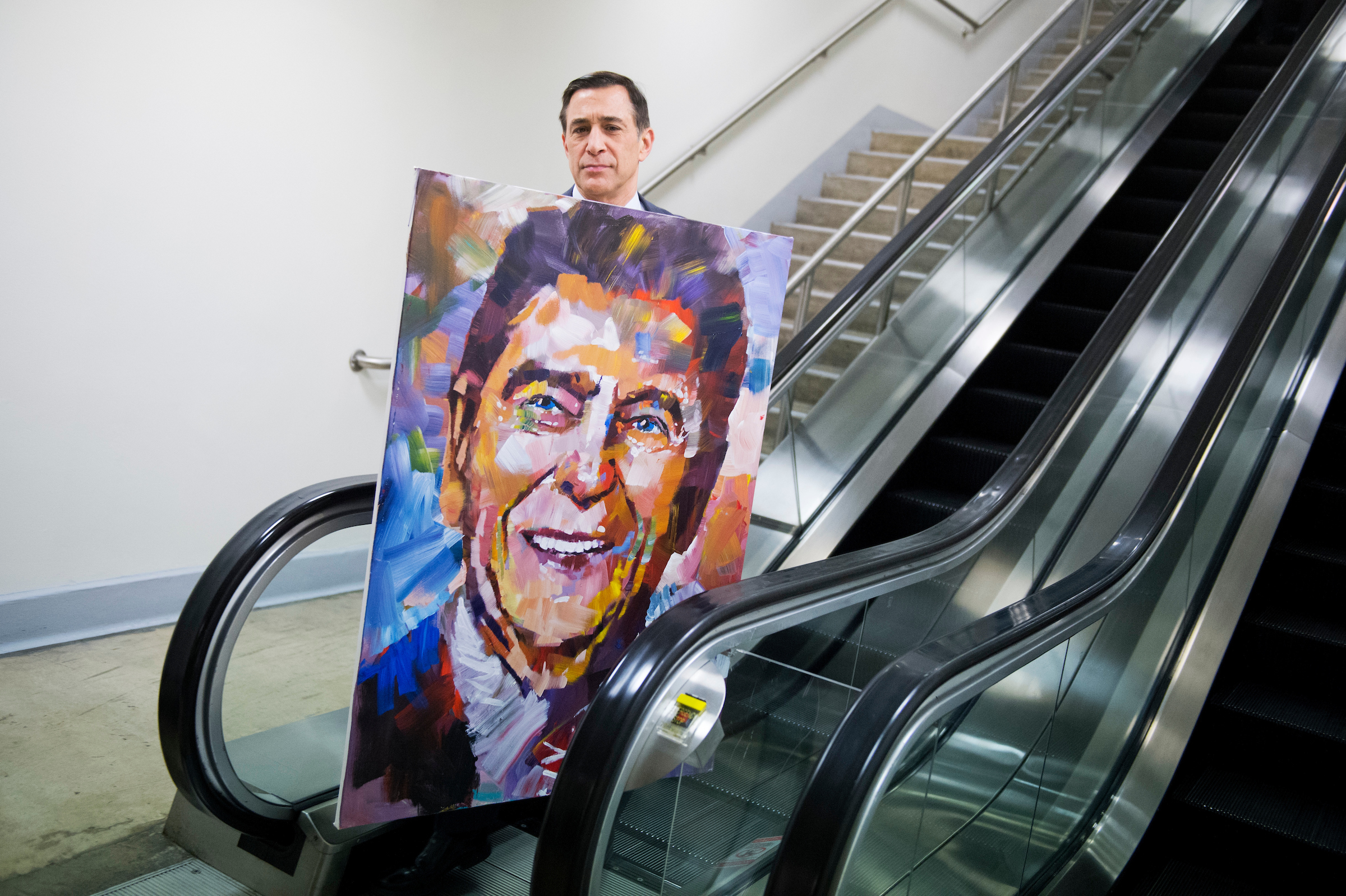 Rep. Darrell Issa walks through the basement of the Capitol with a painting of fellow Californian former President Ronald Reagan. (Tom Williams/CQ Roll Call File Photo)