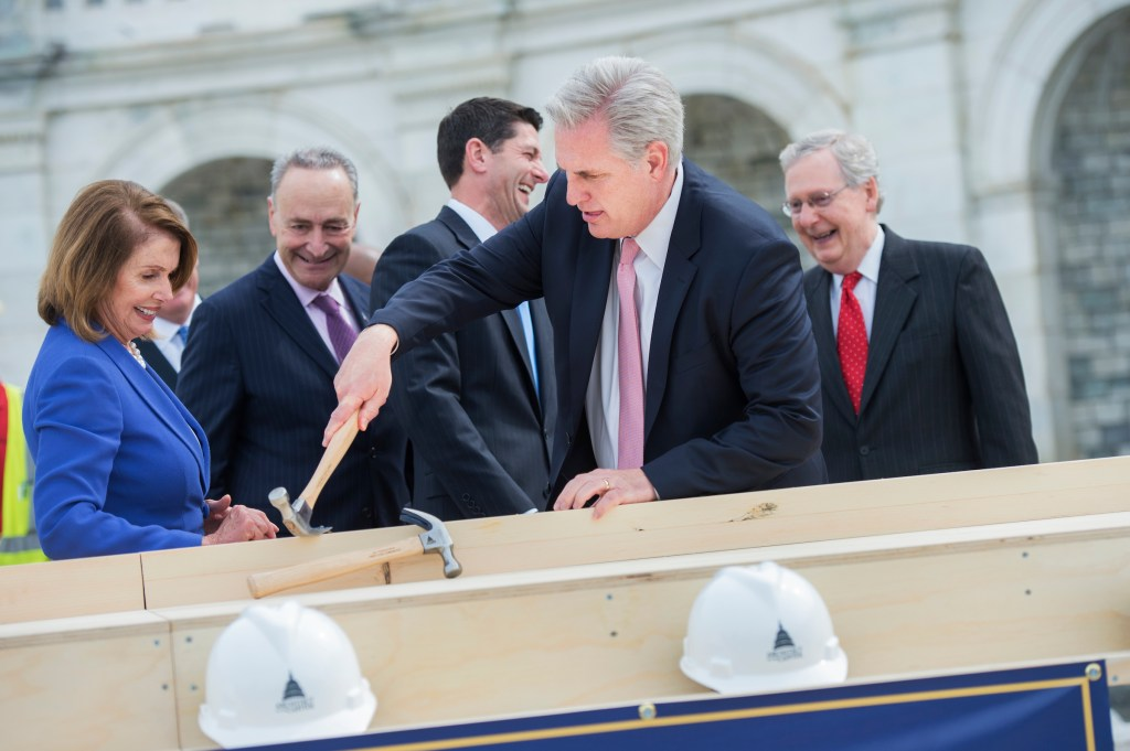McCarthy, as other congressional leaders look on, removes Schumer's nail from the plank. (Tom Williams/CQ Roll Call)