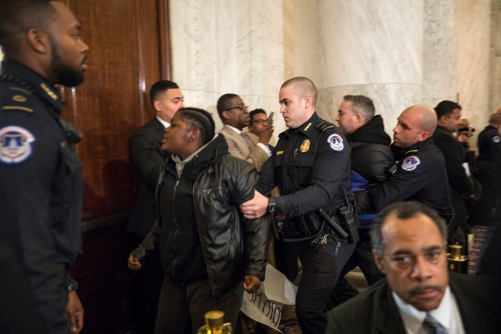 Protesters being removed from the hearing. (Photo courtesy of Jim Lo Scalzo/ European Pressphoto Agency)
