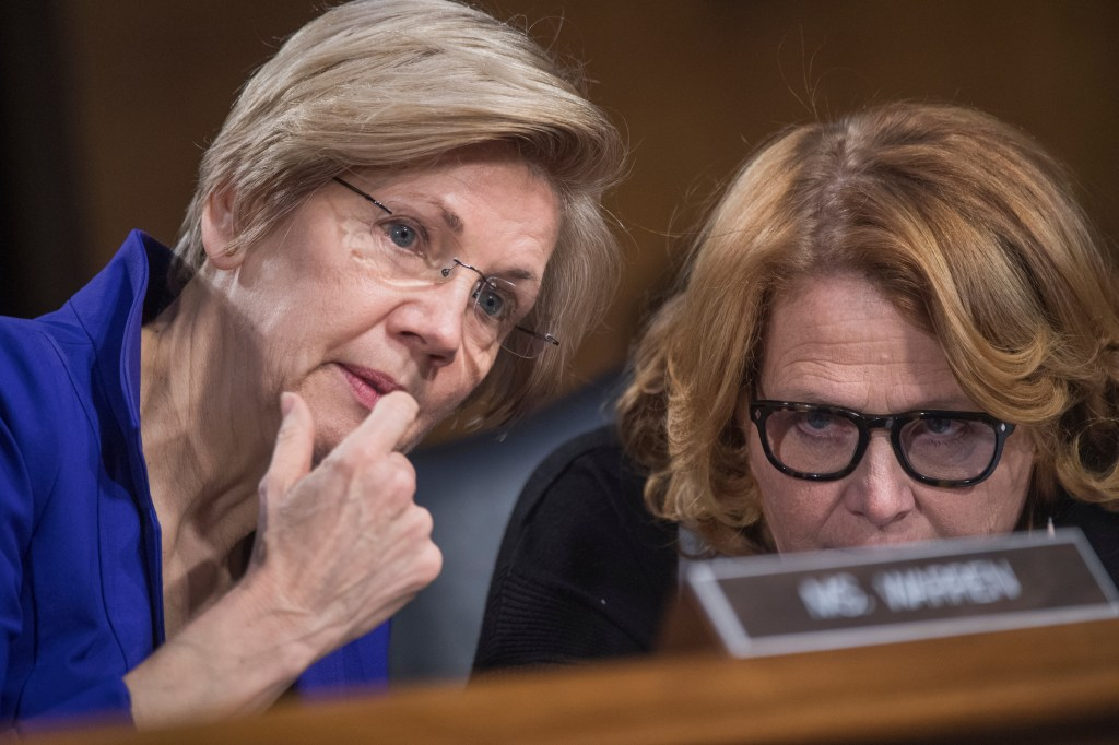 UNITED STATES - FEBRUARY 14: Sens. Elizabeth Warren, D-Mass., left, and Heidi Heitkamp, D-N.D., talk during a Senate Banking, Housing, and Urban Affairs Committee hearing in Dirksen Building titled
