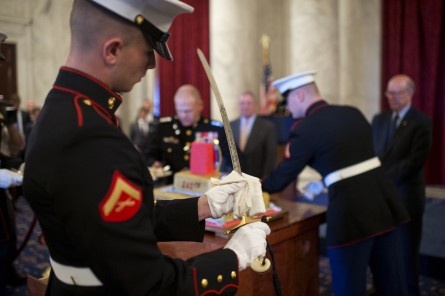 A Marine cleans the sword used to cut the cake during a 240th birthday celebration for the Marine Corps. (Tom Williams/CQ Roll Call)