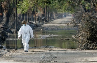 A woman wears protective clothing while walking down a street in the Lakefront district of New Orleans three weeks after Hurricane Katrina.  (Justin Sullivan/Getty Images File Photo)