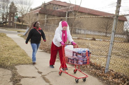 UNITED STATES - FEBRUARY 22: Virginia Mitchell, right, and her daughter-in-law Tiara Williams leave the the Sylvester Broome Center in Flint, Mich., after receiving cases of bottled water, February 22, 2016. The center is being used for water distribution and health care services. The water supply was not properly treated after being switched from Lake Huron to the Flint River and now contains lead and iron. (Photo By Tom Williams/CQ Roll Call)
