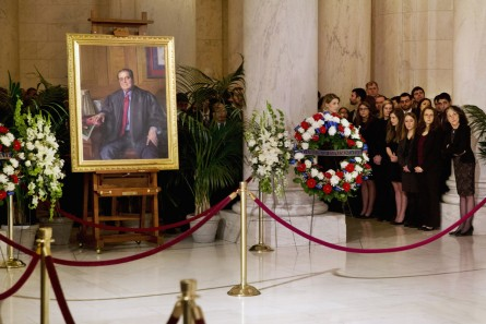 Law clerks and Supreme Court staff watch a private ceremony in the Great Hall of the Supreme Court where late Supreme Court Justice Antonin Scalia lies in repose in Washington, Friday Feb. 19, 2016. At left is a portrait of Scalia. (AP Photo/Jacquelyn Martin, Pool)