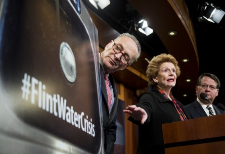 Schumer, Stabenow and Peters look at poster showing dirty water in Flint during the Senate Democrats' news conference on the lead contaminated drinking water. (Bill Clark/CQ Roll Call)