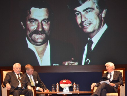 Walesa, far left, and Dodd, far right, discuss the Cold War under gigantic images of their previous selves. (Photo courtesy of the Embassy of Poland)