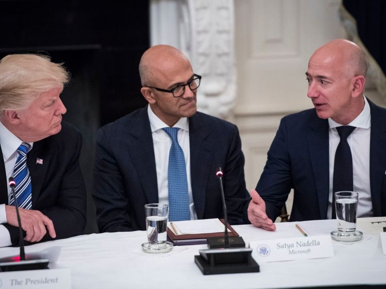 President Trump and Microsoft CEO Satya Nadella listen to Amazon CEO Jeff Bezos speak. All three are seated at a conference table.
