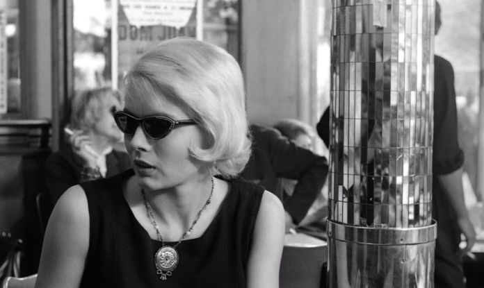 Cléo sits in a cafe, startled, in Cléo from 5 to 7