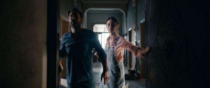 Olga Kurylenko and Kevin Janssens explore a dark corridor of their house in the horror movie The Room.