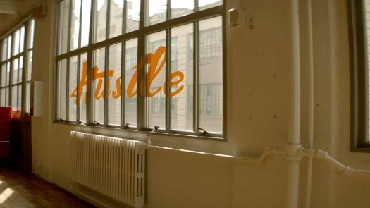 """A window printed with cursive lettering reading """"Hustle."""""""