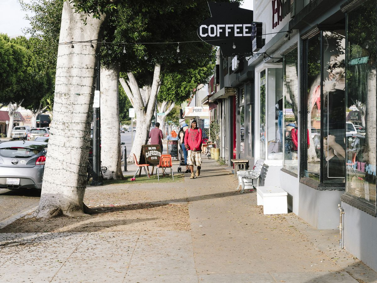 """Small business storefronts, one with a black and white sign for """"coffee,"""" on a tree-lined street."""