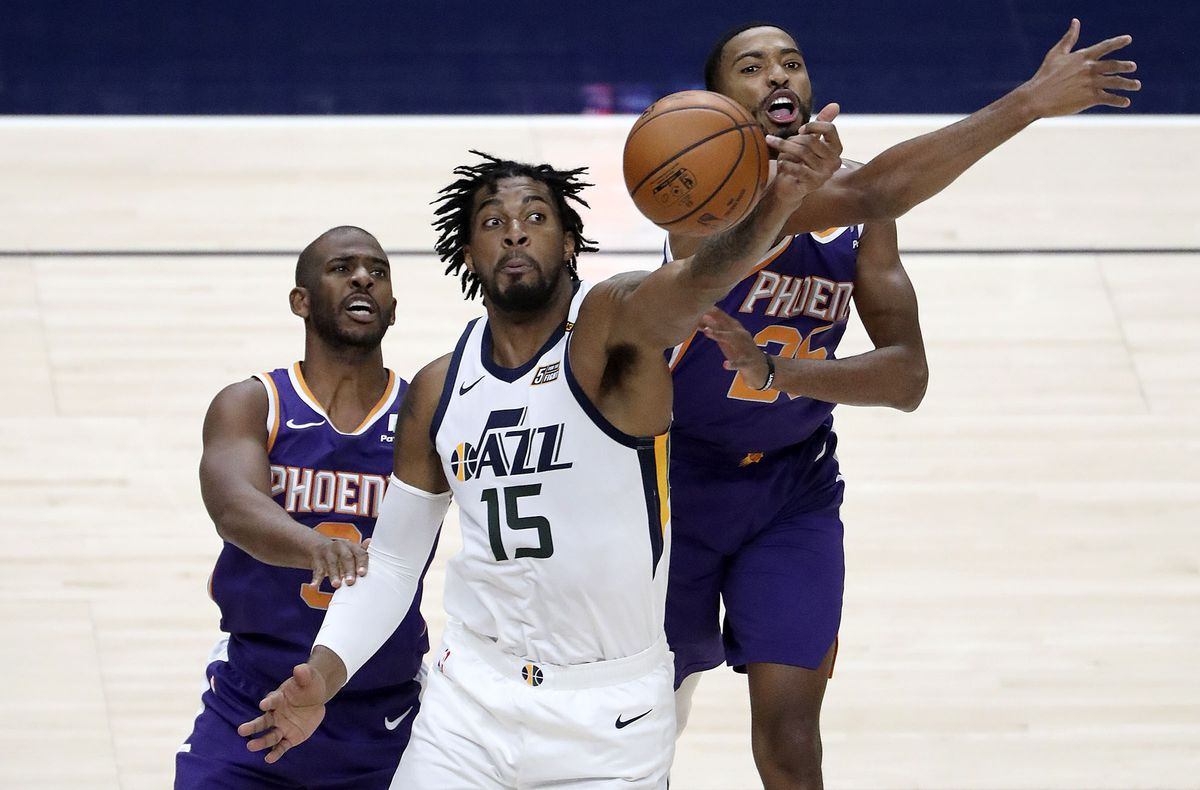 Utah Jazz center Derrick Favors (15) reaches for the ball in front of Phoenix Suns guard Chris Paul (3) and Phoenix Suns forward Mikal Bridges (25) during a preseason NBA game at the Vivint Smart Home Arena in Salt Lake City on Monday, Dec. 14, 2020.