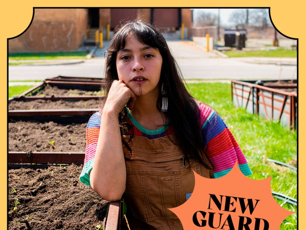 A person wearing overalls since next to gardening plots