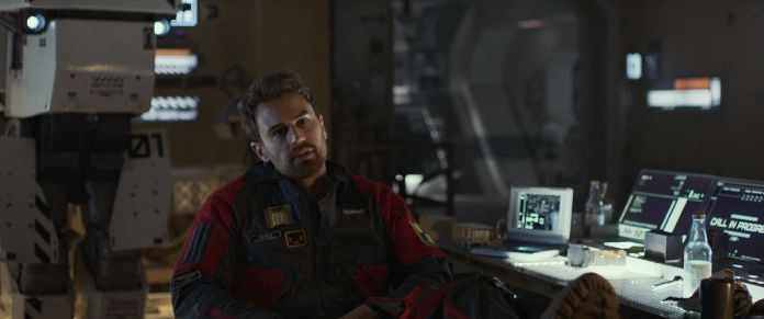 Theo James leans back with his feet on his messy tech-desk and his prototype robot J1 in the background in Archive.