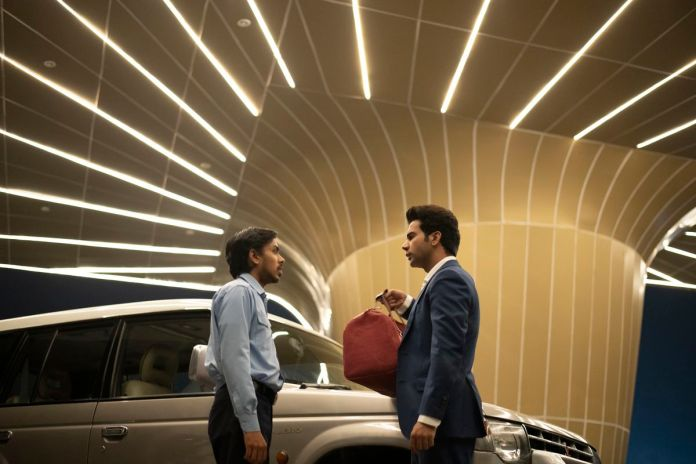 Adarsh Gourav and Rajkummar Rao face each other under a carport striped with neon lights in The White Tiger.