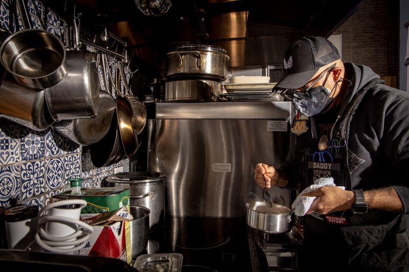 A man in a mask stirs a sauce in a pot over a stove