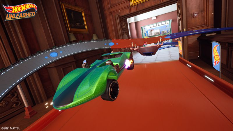 A 1970s-style Hot Wheels racer with golden flake painting takes a long jump