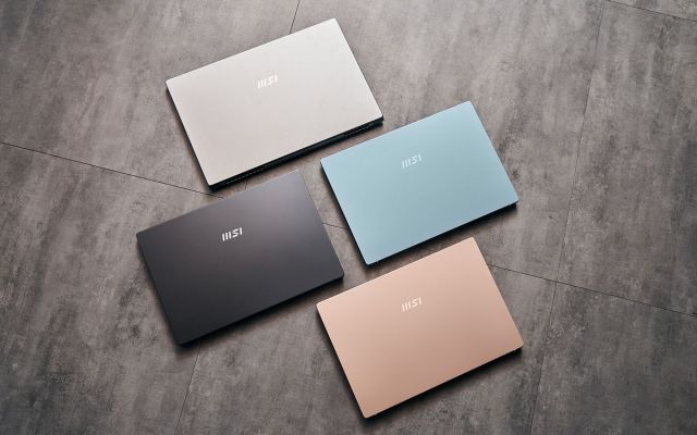 Four MSI Modern laptops arranged on the floor, closed.