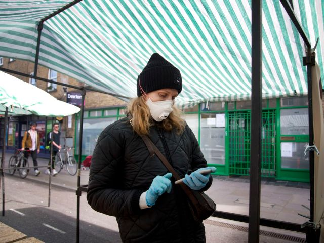 A woman in protective mask and gloves stands in a market tent and looks at her phone.