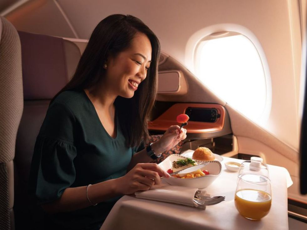 Woman seated on an airplane eating a luxury meal.