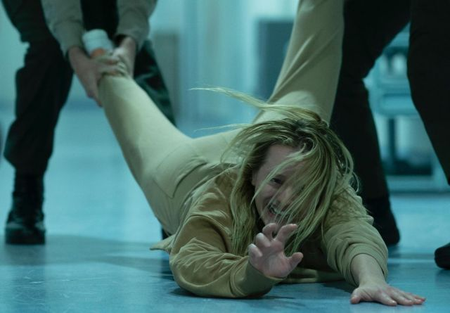 A wild-haired blonde woman, grimacing in distress, is dragged along the floor by her feet by two people only seen from the waist down.