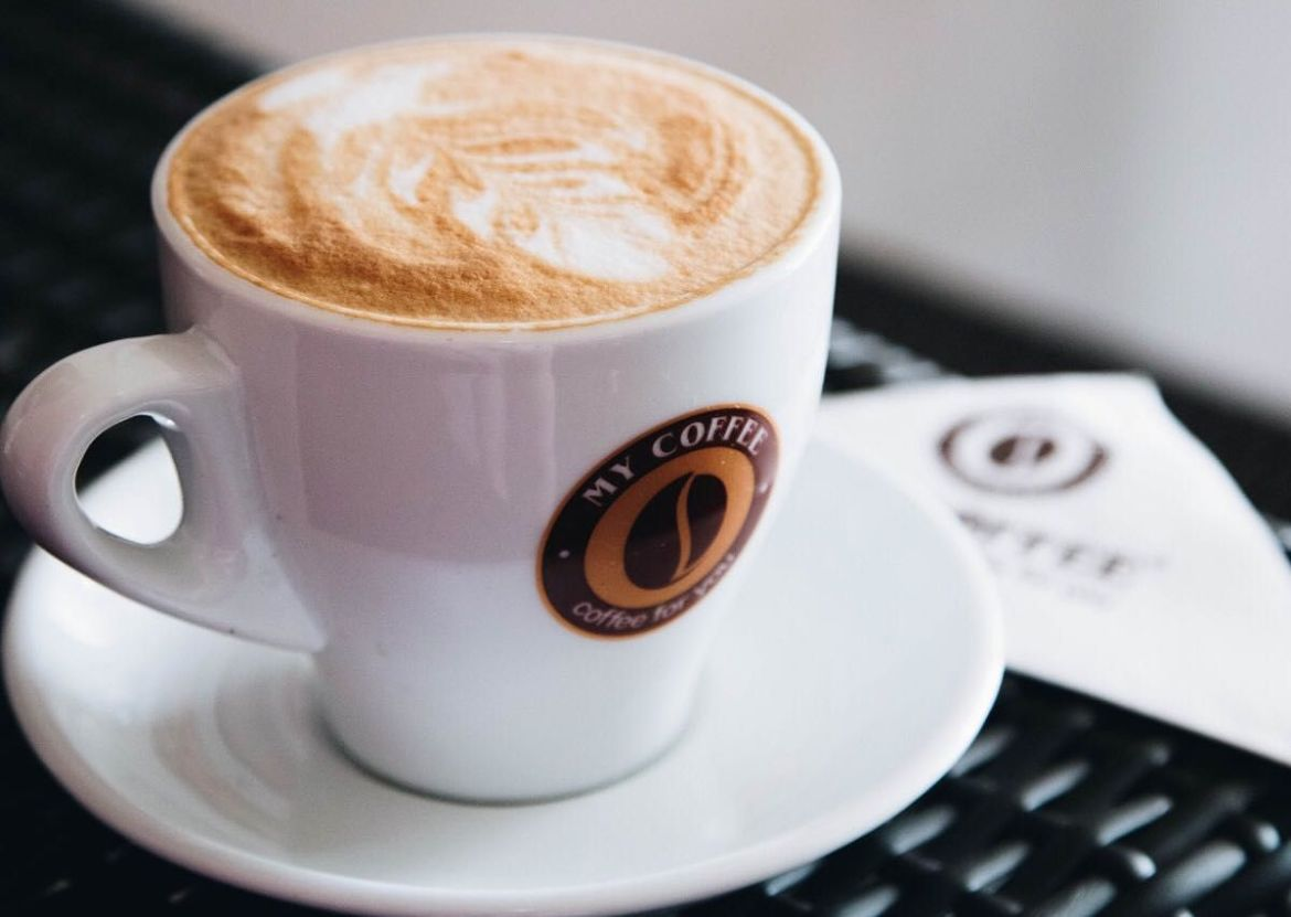 A frothy cappuccino in a branded My Coffee Wings mug on a white saucer beside a folded branded paper napkin