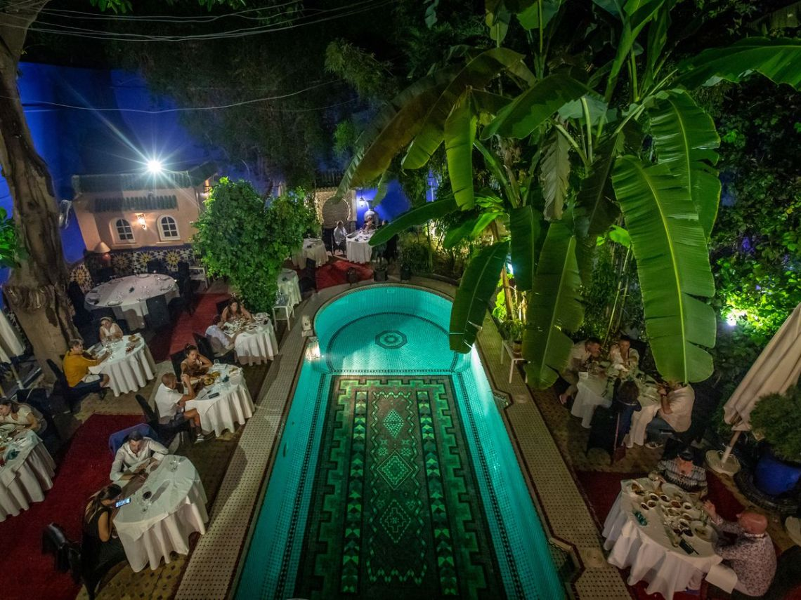 From a high perch, a large pool with a decorative floor in the middle of an interior courtyard/dining room where guests are seated at tables with white tablecloths, large palm trees reach toward the camera, and small structures imitate exterior buildings