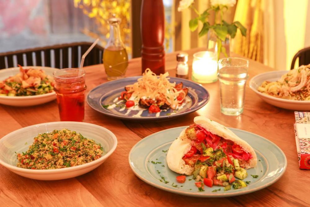 A candle-lit table set with several ceramic plates with different dishes including a grain salad and pita sandwich