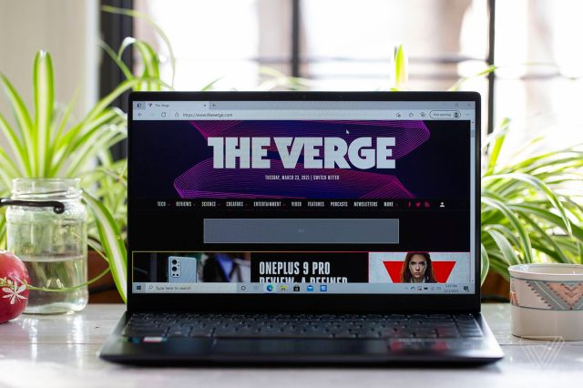 The MSI Prestige 14 Evo from the front, open. The screen displays The Verge homepage. A mug is on its right and a ball and a mason jar half filled with water are on its left. In the background are plants.
