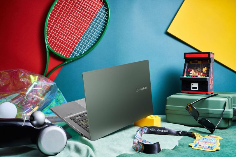 The VivoBook S14, open, faces away from the camera next to a pile of accessories including a tennis racket, a toolbox, and a pair of sunglasses.