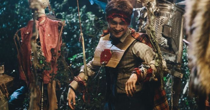 Daniel Radcliffe, wearing cardboard armor and being puppeted through a set made of trash gathered to represent people on a bus, plays a living corpse in Swiss Army Man.