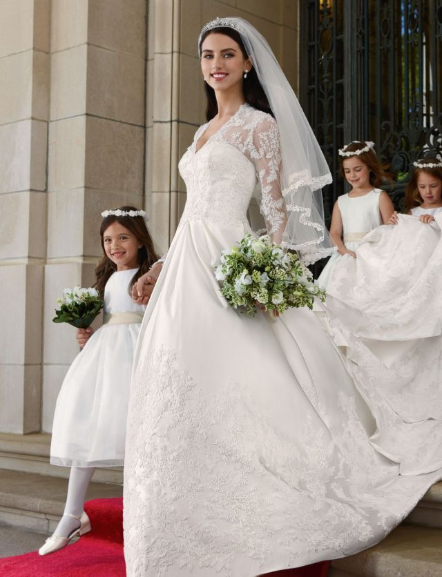 A model wearing a dress just like Kate Middleton's wedding dress steps through a door onto a red carpet, three children at her side.