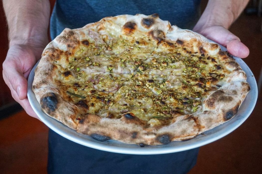 A blistered pizza with light cream and pistacio.