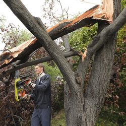 Collin Stanley cuts branches from a tree that was snapped by high winds in his Salt Lake neighborhood on Tuesday, Sept. 8, 2020.