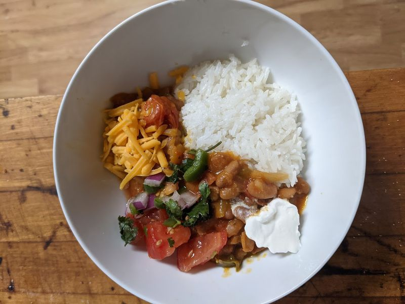 A white bowl holds beans, rice, and salsa.