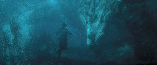 Shang-Chi (Simu Liu) floats underwater in front of a huge Chinese dragon, the Great Protector in Shang-Chi and the Legend of the Ten Rings.