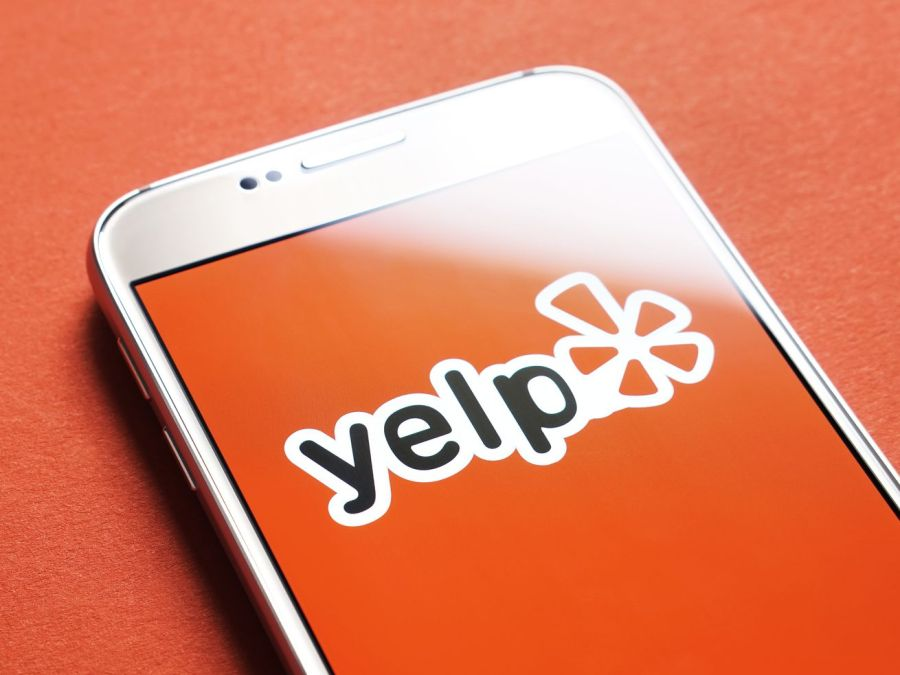 Yelp logo on a phone with red background.