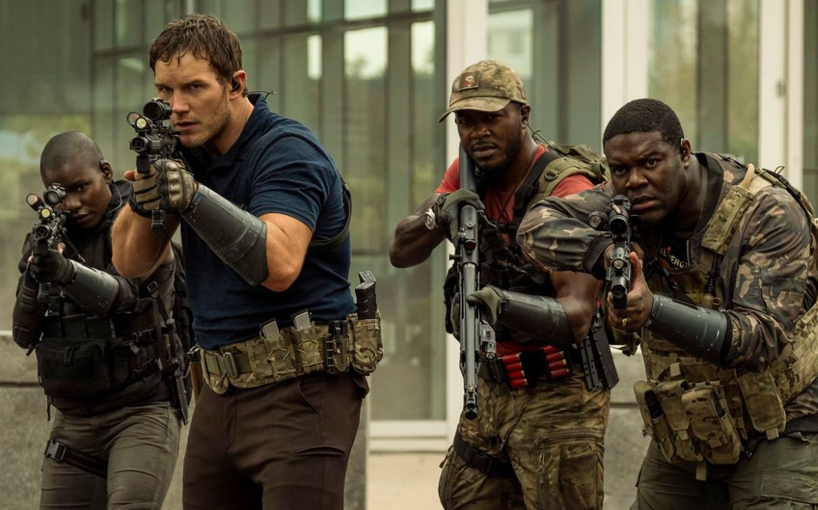 Chris Pratt stands meaningfully at the head of a small group of armed and camo-wearing soldiers, all of whom are Black except him