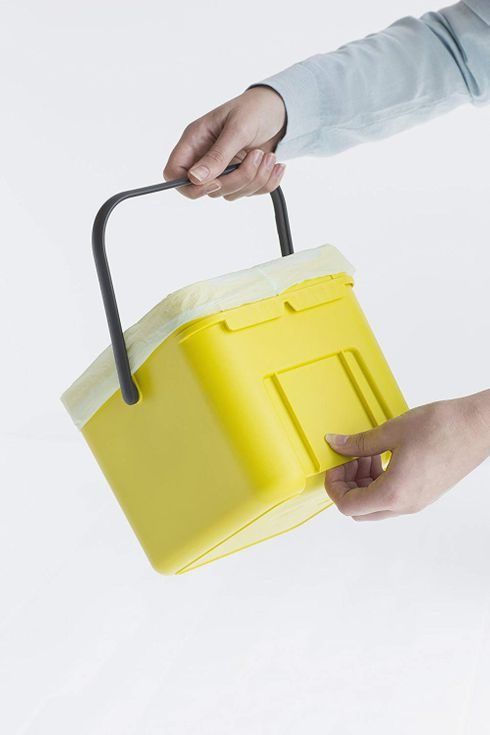Someone holding a yellow waste bin