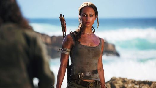 Alicia Vikander as Lara Croft, in tanktop and carrying bows while standing in front of the ocean, in the 2018 Tomb Raider movie