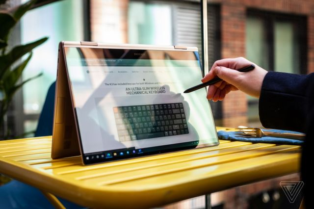 A user uses the Galaxy Book Pro 360 in tent mode on an outdoor picnic table with the S-Pen. The screen displays a mechanical keyboard review on The Verge.