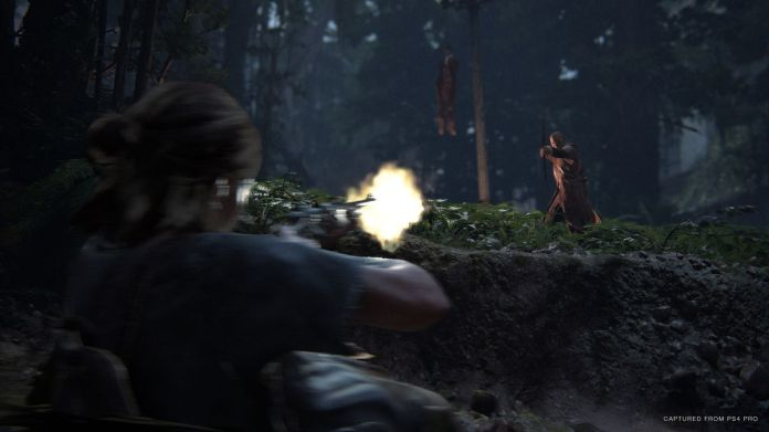 Ellie fires a gun at a hazy enemy in The Last of Us Part 2, with a corpse hanging from a tree behind him