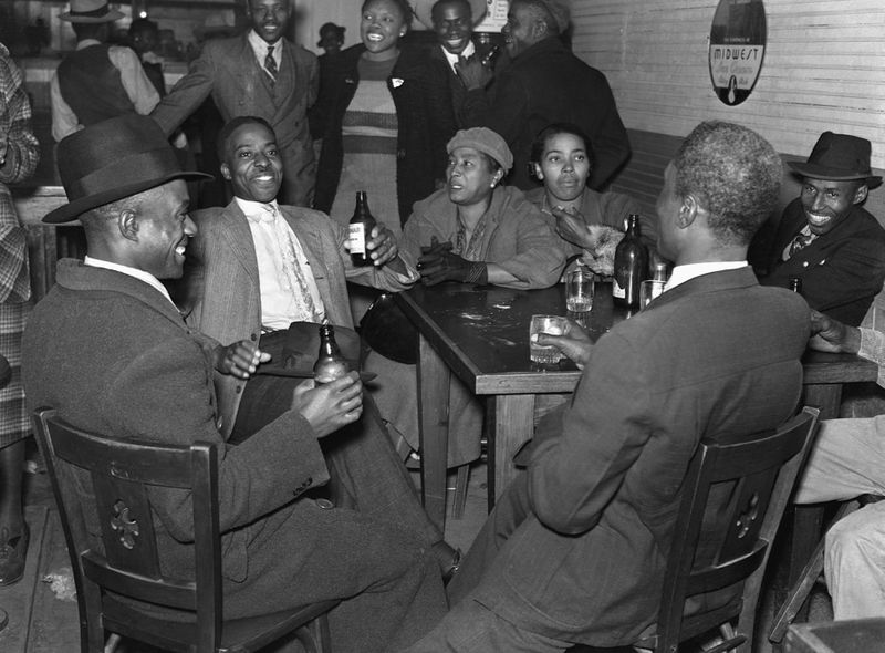 Black and white photo of people sitting around a table, with bottles of beer on the tabletop.
